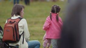La petite fille parle pour enfanter et joue avec la poupée sur l'herbe au festival serré banque de vidéos