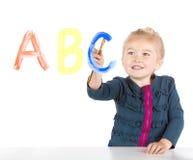 La petite fille peint des lettres sur l'hublot Images stock