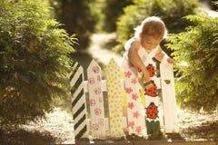 La petite fille peint la barrière Photo stock