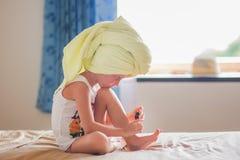 La petite fille peint ses ongles de pied à la maison Photo stock