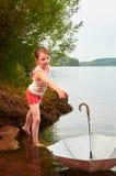 La petite fille a perdu son parapluie dans le jour nuageux dans le lac Image stock