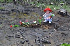La petite fille plante des tulipes au-dessus de la terre brûlée Photographie stock libre de droits