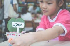 La petite fille plante une usine d'amour de coeur Photos stock