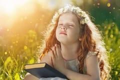 La petite fille a plié sa main et ferme vos yeux dans la prière, drea photos stock