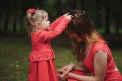 La petite fille porte la mère de guirlande Image stock
