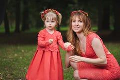 La petite fille porte la mère de guirlande Photo libre de droits