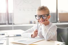 La petite fille positive d'affaires travaille dans le bureau Photographie stock
