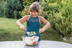 La petite fille prépare diligemment la salade dans le jardin Photographie stock libre de droits