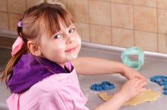 La petite fille prépare un gâteau dans la cuisine Photographie stock libre de droits