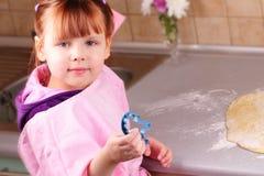 La petite fille prépare un gâteau dans la cuisine Photo libre de droits