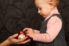 La petite fille prend des jouets de Noël des mains Photos stock
