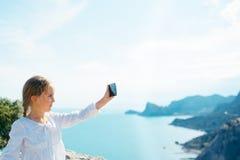 La petite fille prend la photo sur le smartphone photos libres de droits