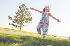 La petite fille, rebondissant, court le long du pré image libre de droits