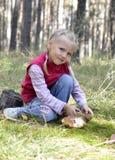 La petite fille recueille des champignons de couche Photographie stock