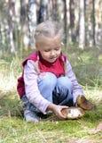 La petite fille recueille des champignons de couche Photos libres de droits
