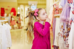 La petite fille regarde avec l'intérêt sur des robes Photo libre de droits