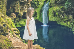 La petite fille regarde l'eau de sourire par une rivière Photos stock