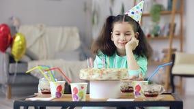 La petite fille regarde le gâteau banque de vidéos