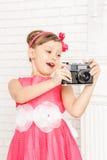 La petite fille regarde le rétro appareil-photo Images stock