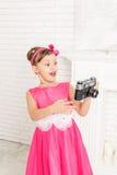 La petite fille regarde le rétro appareil-photo Images libres de droits