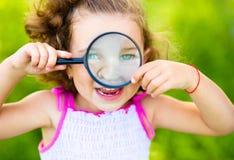 La petite fille regarde par la loupe photo stock