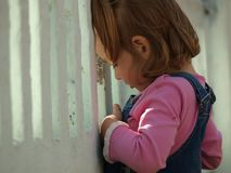 La petite fille regarde par une barrière blanche images libres de droits