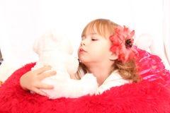 La petite fille regarde un ours de nounours Images stock