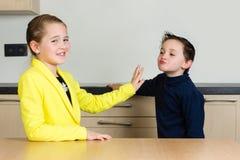La petite fille rejette le petit garçon essayant de l'embrasser Images stock
