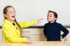 La petite fille rejette le petit garçon essayant de l'embrasser Image libre de droits