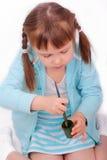 La petite fille remue la peinture avec un balai Image libre de droits