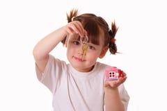 La petite fille retient une clé dans sa main Photographie stock