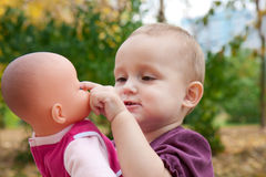 La petite fille retient une poupée Photographie stock