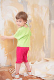 La petite fille retirent de vieux papiers peints du mur Photographie stock libre de droits