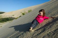La petite fille a roulé vers le bas des dunes de sable de Te Paki Photo libre de droits