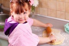 La petite fille roule la pâte Images libres de droits