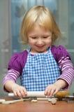 La petite fille roule la pâte Photo stock