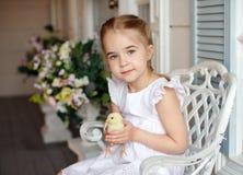 La petite fille rousse avec des tresses tenant un chicke jaune Photographie stock libre de droits
