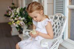 La petite fille rousse avec des tresses tenant un chicke jaune Photos stock