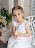 La petite fille rousse avec des tresses tenant un chicke jaune Photo stock