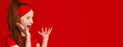La petite fille rousse avec un bandage sur ses cheveux dans un T-shirt rouge crie heureusement quand elle voit quelque chose au c photo stock
