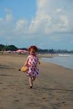 La petite fille rousse mignonne court sur la plage de Bali Image stock