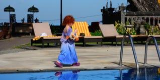 La petite fille rousse mignonne dans le T-shirt de son papa marche le long de la piscine photo libre de droits