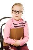 La petite fille sérieuse en glaces avec un livre Photos libres de droits