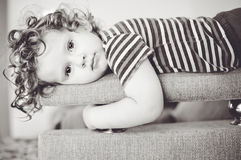 La petite fille s'étend sur un sofa. photos stock