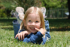 La petite fille s'étendant sur une herbe Photo stock