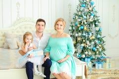 La petite fille s'asseyant avec le père heureux et la mère enceinte sur le lit près a décoré l'arbre de Noël photo libre de droits