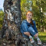 La petite fille s'asseyant dans les bois s'approchent du bouleau nature Photo libre de droits
