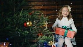 La petite fille s'asseyant sous l'arbre de Noël et apprécie le cadeau banque de vidéos