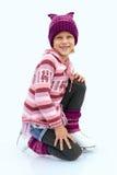 La petite fille s'asseyant sur la glace dans le patinage de glace Isolant Photo stock