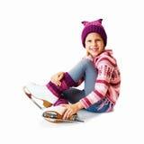 La petite fille s'asseyant sur la glace dans le patinage de glace Isolant Images stock